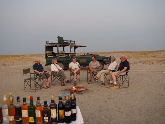 Botswana mobile group of friends 50+ vehicle on pans sunset campfire